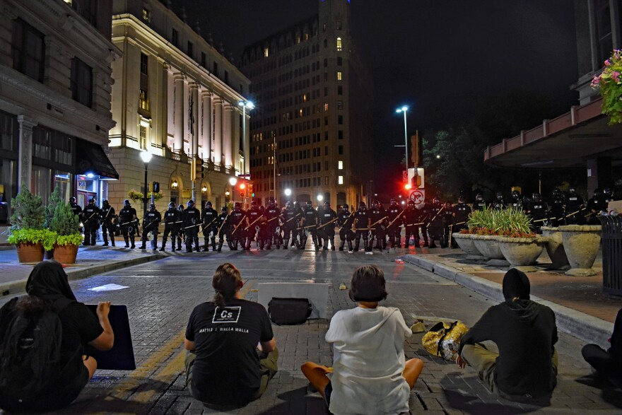 Protesters remain seated before police officers in downtown San Antonio.