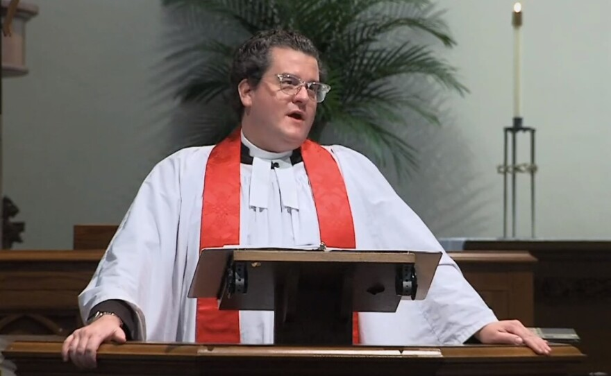 A priest in a white robe talks at a lectern