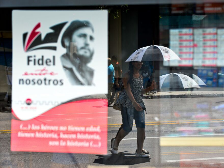 A woman in Havana walks next to a poster about Cuban former President Fidel Castro in August.