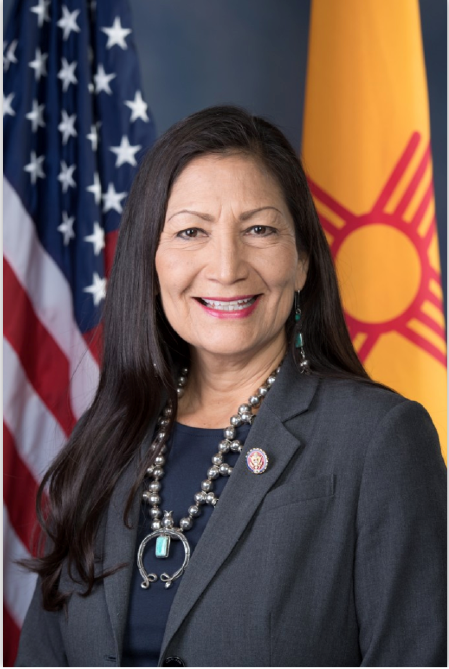 Deb Haaland smiles for an official headshot wearing a dark grey suit jacket and a statement of a metal necklace.