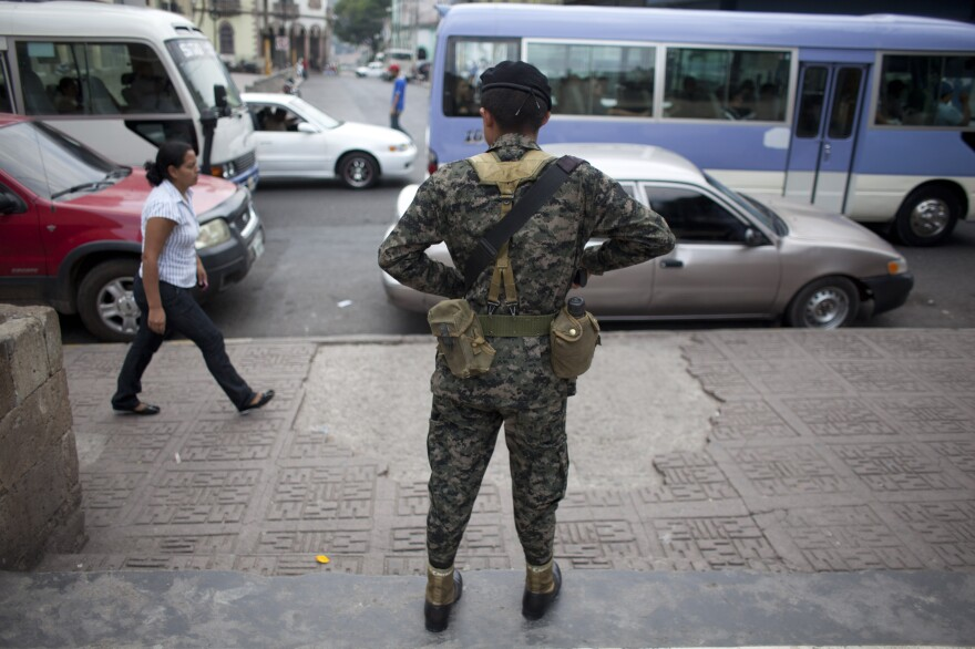 A soldier watches over public transport users during an operation in Tegucigalpa, Honduras, in April. The crime rate is soaring in Honduras, and corrupt and ineffective law enforcement is widely seen as part of the problem.