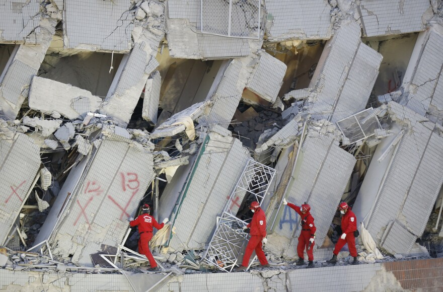 Emergency rescuers search for missing in a collapsed building on Sunday.