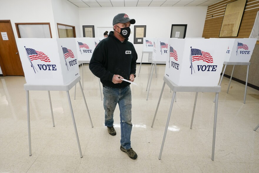 Chris Helps, of Earlham, Iowa, makes his way to the ballot box during early voting, Tuesday, Oct. 20, in Adel, Iowa.