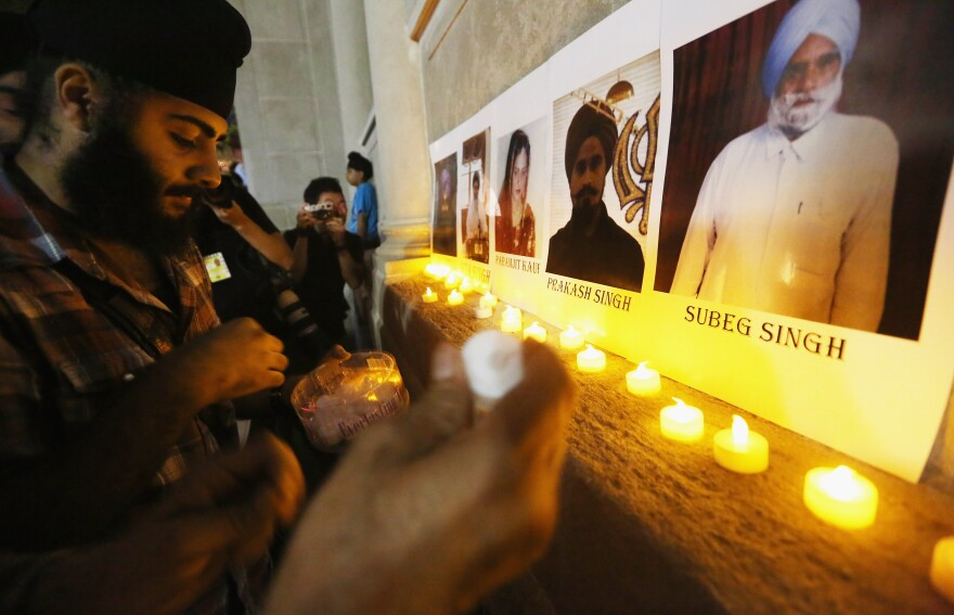 Photos of victims are seen during a candlelight vigil in Union Square for victims of the Wisconsin Sikh temple shooting on August.