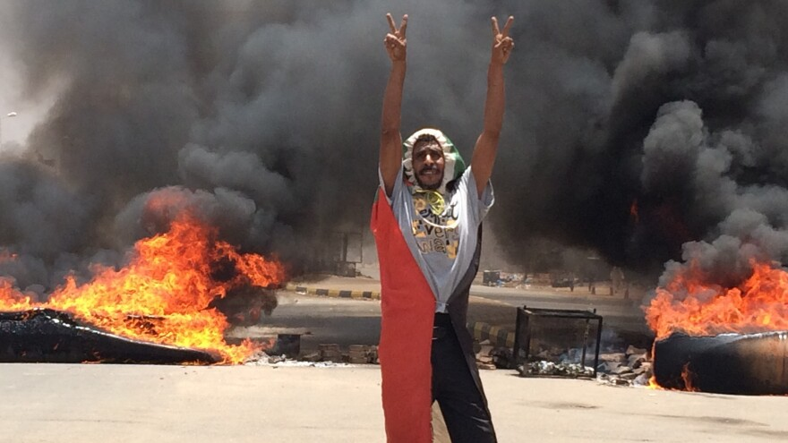 A protester flashes the victory sign in front of burning tires and debris near Sudan's military headquarters. For months demonstrators have been demanding a a transition to civilian rule.