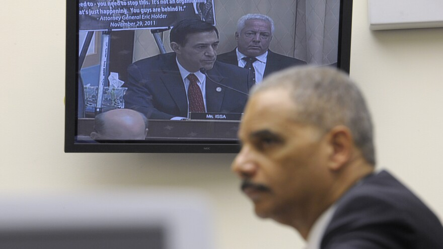 Attorney General Eric Holder listens to Rep. Darryl Issa, R-Calif., on video screen, while testifying on Capitol Hill in Washington, Thursday, Dec. 8, 2011, before a House Judiciary Committee hearing on Operation Fast and Furious.