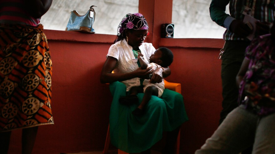 A caretaker holds baby Sekou Dukuly at a shelter run by ChildFund in Monrovia. Later that day, the baby was reunited with his extended family.