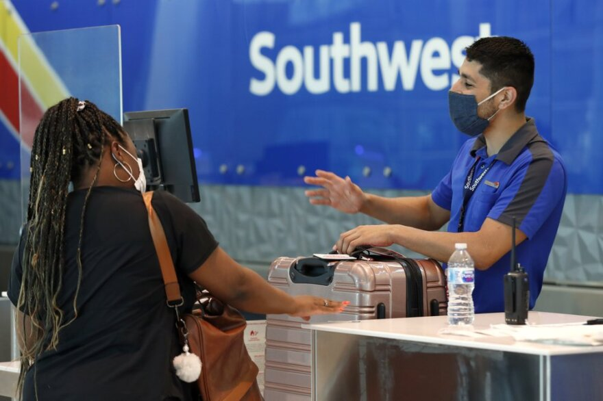 Southwest airlines employee Oscar Gonzalez, right, assists a passenger at the ticket counter at Love Field in Dallas in June.