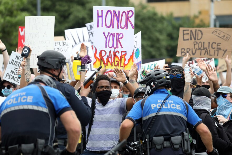 "Demonstrators facing police hold signs saying ""Honor your rage"" and ""End police brutality"" at a protest in downtown Austin on Sunday."