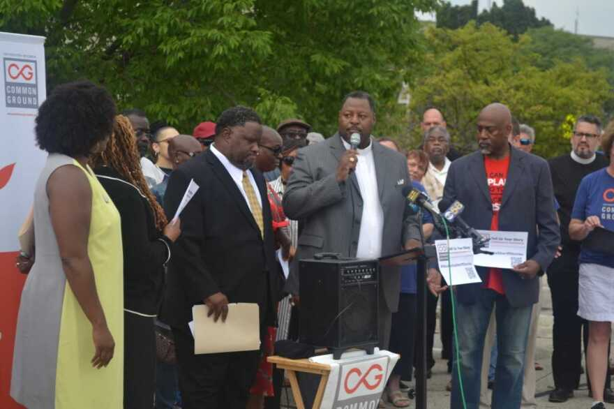 Demetrius Williams of Community Baptist Church in Milwaukee and John K. Patterson (with microphone) of Mt. Olive Baptist Church in Milwaukee speak during an event organized by Common Ground. (Courtesy Common Ground)