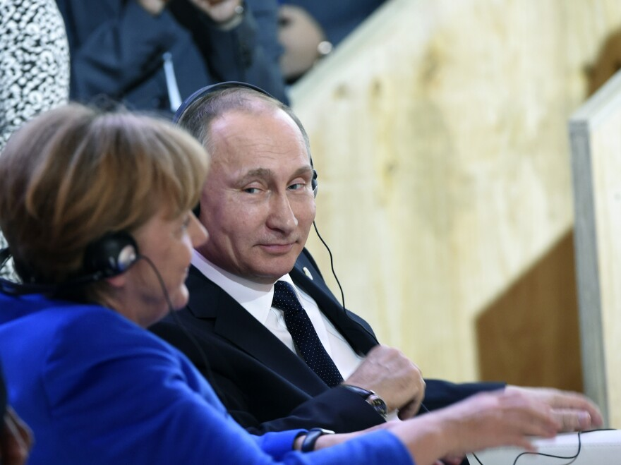 """""""I trust her, she is a very open person,"""" Vladimir Putin said of German Chancellor Angela Merkel, seen here at last month's climate talks in Paris. But, he told the German daily <em>Bild</em>, """"she is also subject to certain constraints and limitations."""""""