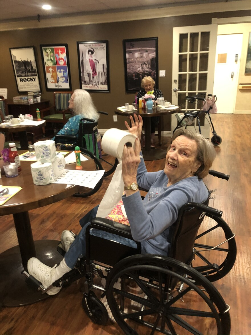 A nursing home resident at NHC Healthcare Maryland Heights wins a roll of toilet paper at a bingo game in March 2020.