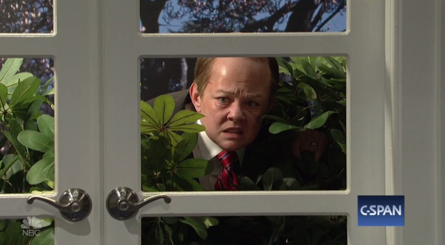 "Melissa McCarthy as ""Spicey"" hides in the bushes from reporters during a White House briefing, led by Aidy Bryant's impersonation of Spicer's real-life stand-in last week, Sarah Huckabee Sanders."