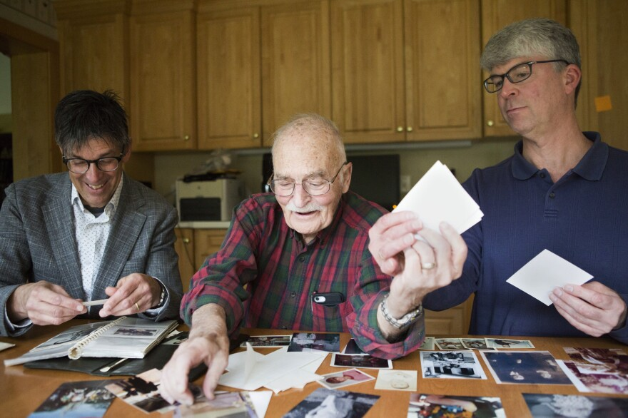 Bruce Auster (left), with his father, Stanley, and his brother, Gordon, look at family photographs at Gordon's home in Kildeer, Ill. A decades-old recording of Bruce's mother trying to convince Gordon that Santa Claus is real has brought back memories for the family.