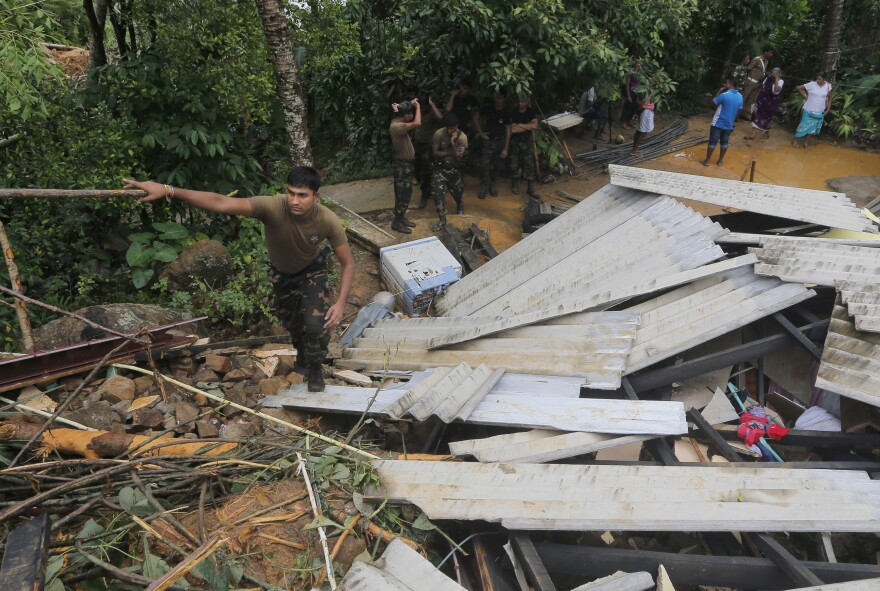 A Sri Lankan army soldier walks on the debris of a house during a search operation in Elangapitiya village in Aranayake, some 45 miles north of Colombo, Sri Lanka, on Thursday.