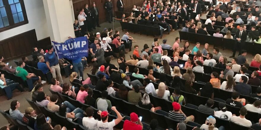 Cheering and clapping ensues when two men begin waving a Trump banner in the aisles of the University Auditorium.