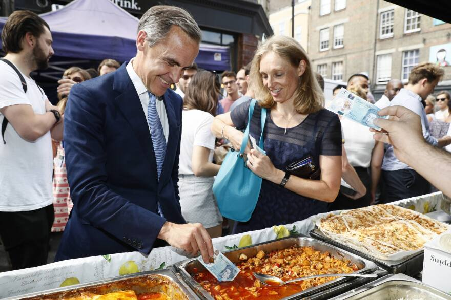 The governor of the Bank of England, Mark Carney, tests the polymer 5-pound note as he buys lunch in London on Tuesday.