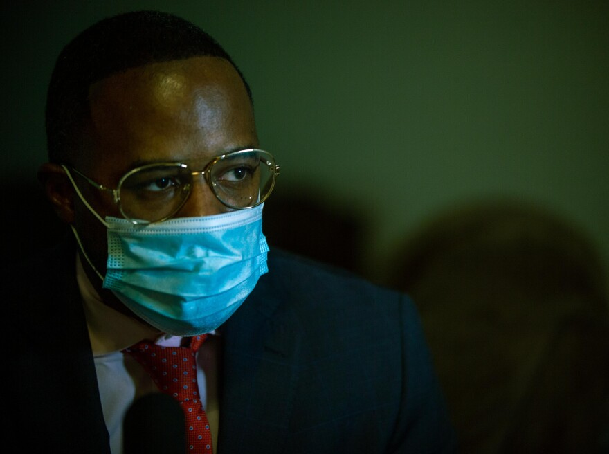 A man in a suit wears a face masks as he stares off-camera