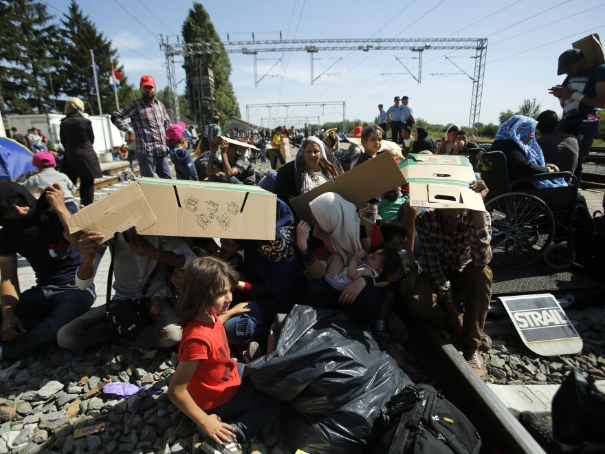 Migrants hide from the sun using cardboard as they sit on the railway track in Tovarnik, Croatia, on Thursday, after arriving there from neighboring Serbia.