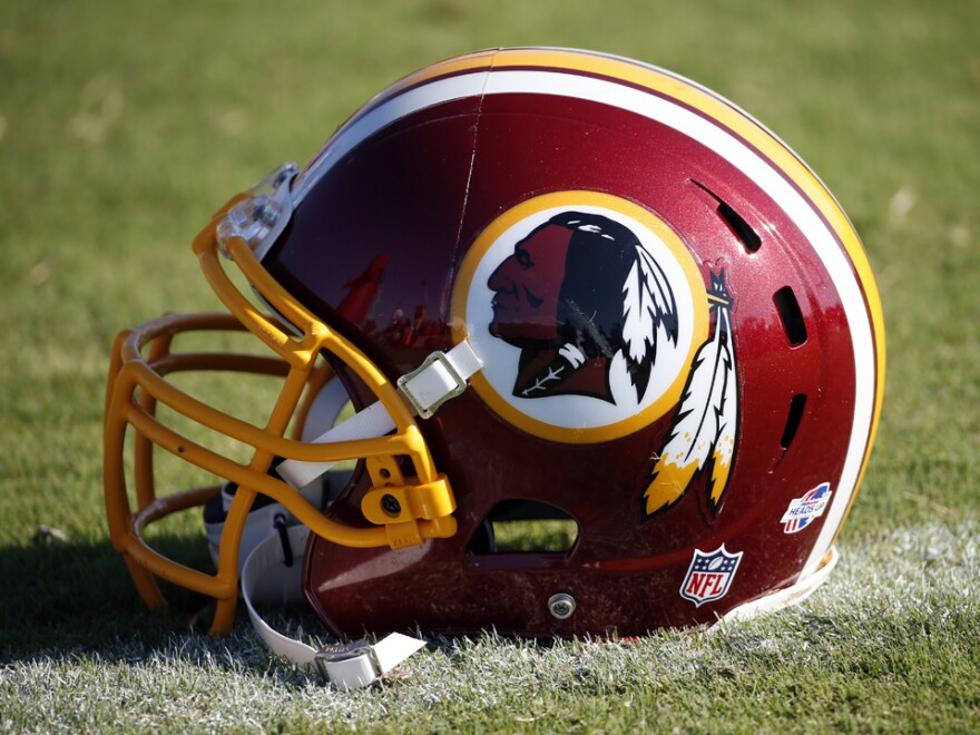 A Washington Redskins helmet lies on the turf at the football team's training facility in Richmond, Va.