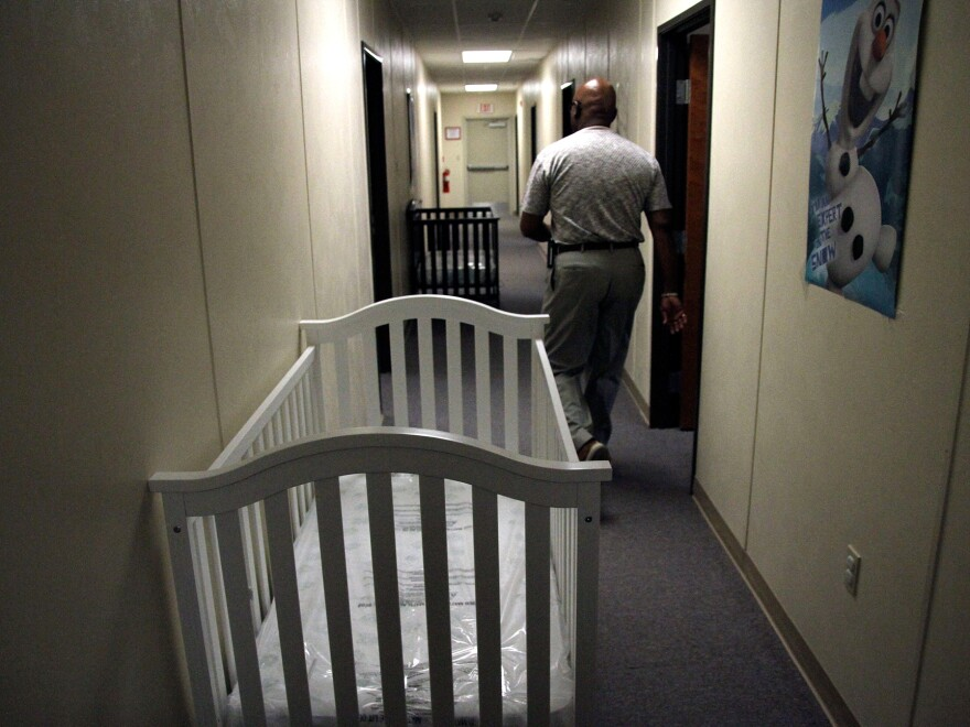 A federal employee walks past cribs inside the Artesia detention center in June.
