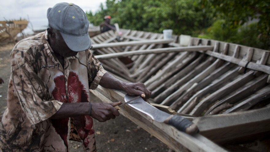 In Leogane, Haiti, a boat-maker sharpens his machete. The 30-foot-long boats are purchased by smugglers for around $12,000 and then taken to northern Haiti to find passengers.
