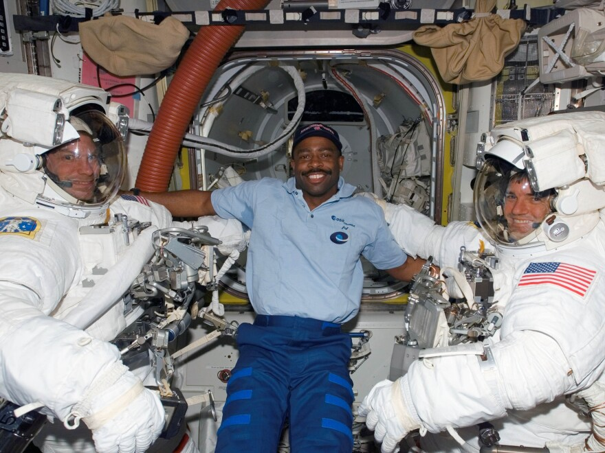 Leland Melvin floats inside the International Space Station alongside astronauts Stanley Love (left) and Rex Walheim, (right) during Melvin's first mission to space.