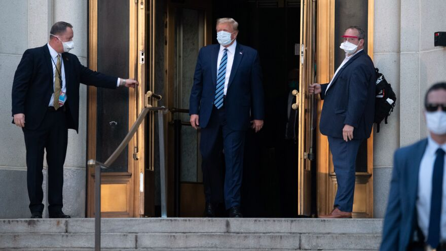 President Trump walks out of Walter Reed Medical Center in Bethesda, Md., before heading back to the White House on Monday evening.