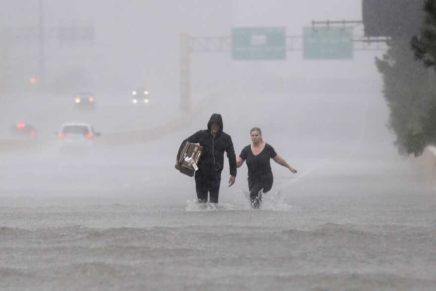Two people walk down a flooded section of Interstate 610 in floodwaters from Tropical Storm Harvey on Sunday.