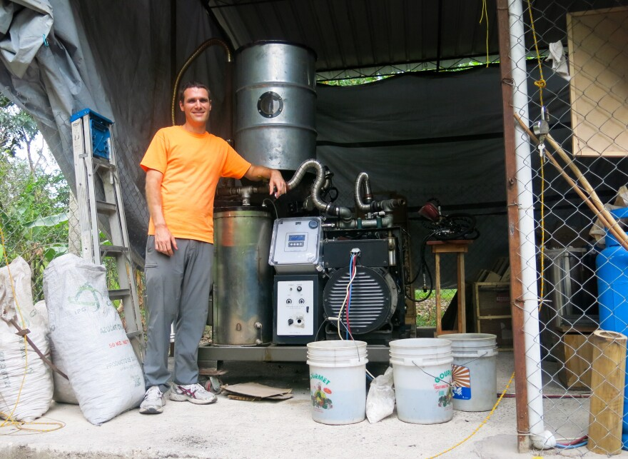 Benjamin Shell helps run the electric company in the village of Tuffet. Behind him is the generator that has given electricity to 30 families so far.