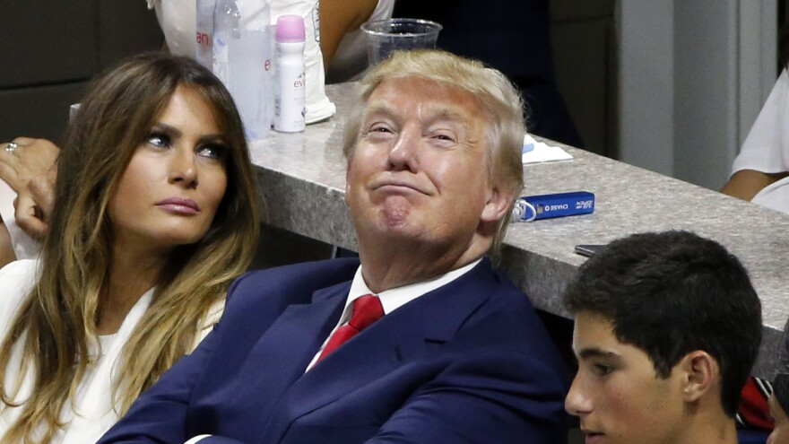 """Donald Trump, seen sitting with his wife, Melania, at the U.S. Open Tennis Championships. He landed in controversy again after he was quoted by Rolling Stone mocking Carly Fiorina and her """"face."""""""