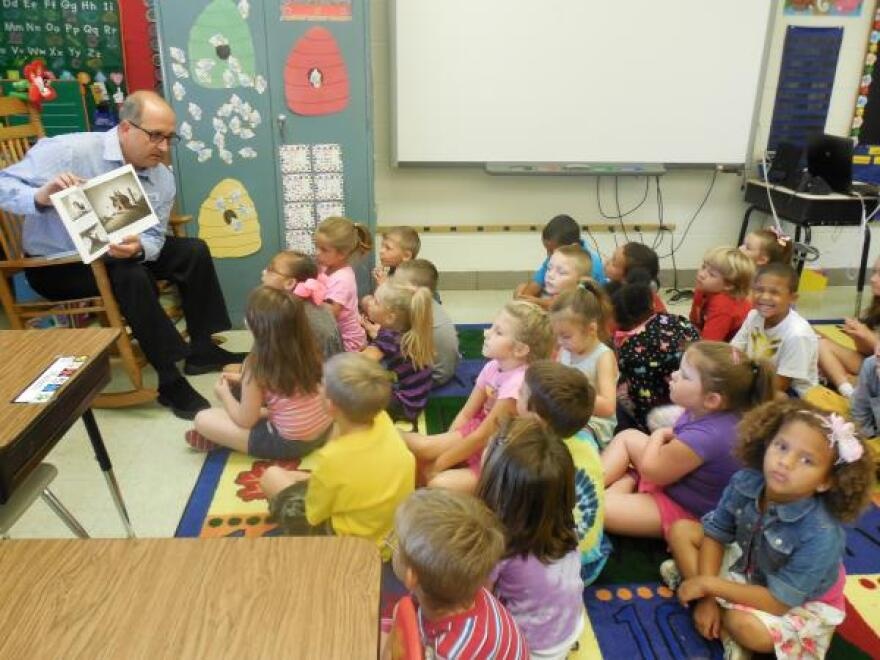 Director of Radio-Interim Bob Powell reads to a kindergarten class at Point Harmony Elementary School.