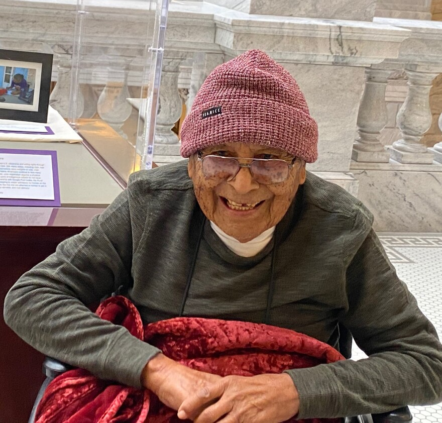An elderly Navajo man in a wheelchair smiles for a photo with marbles columns in the background
