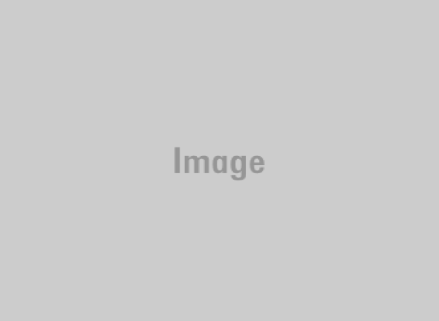 Juan Luis Guerra (center) poses for a photo with José Massó of ¡Con Salsa! (left) and Robin Young of Here & Now. (Courtesy)