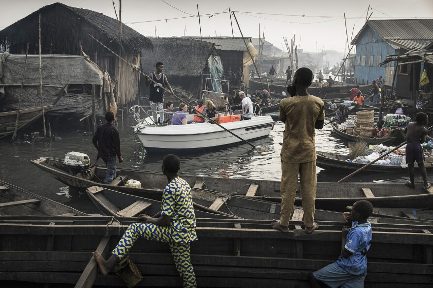 """A group of American expats in Lagos<strong> </strong>is steered through the canals of Makoko, """"a slum €""""on the shores of Lagos, Nigeria."""