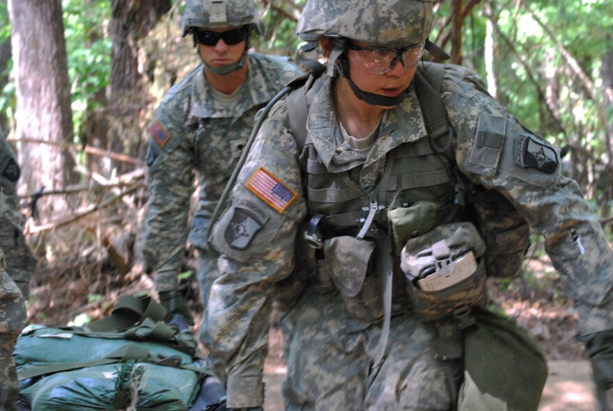 In a May 9, 2012 photo, Capt. Sara Rodriguez, 26, of the 101st Airborne Division, carries a litter of sandbags during the Expert Field Medical Badge training at Fort Campbell, Ky. Female soldiers are moving into new jobs in once all-male units as the U.S. Army breaks down formal barriers in recognition of what's already happened in wars in Iraq and Afghanistan.