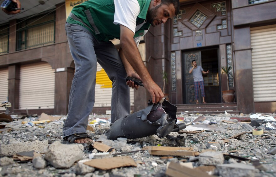 A Palestinian security guard checks the remains of an Israeli missile that hit a building in Gaza City following an airstrike on Friday. Israeli has carried out multiple ground operations in Gaza since 2000 but has never fully suppressed Palestinian rocket fire or closed off smuggling tunnels.