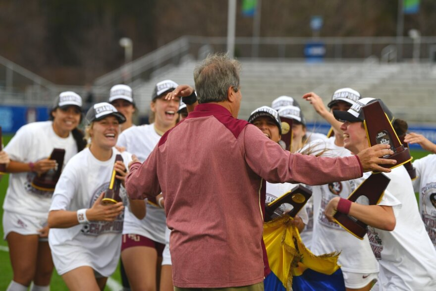 The FSU Soccer team rushes their coach Mark Krikorian after winning the second soccer championship in school history.