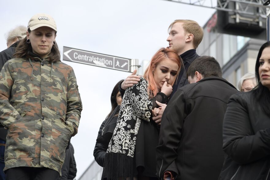 People react near where a truck crashed into the Ahlens department store in central Stockholm on Friday.