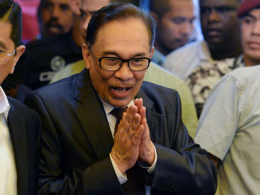 Jailed former opposition leader Anwar Ibrahim gestures before speaking to the media after his return home following his release from hospital in Kuala Lumpur on Wednesday following his royal pardon.