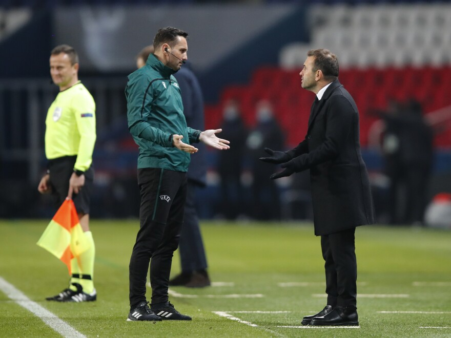 Basaksehir's manager Okan Buruk, right, argues with referee Sebastian Coltescu during a Champions League soccer match between Paris Saint Germain and Istanbul Basaksehir in Paris on Tuesday.