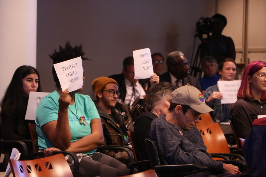 """crowd of people sits down in chairs. Three people hold up paper signs with the words, """"Protect our LGBTQ+ youth"""" printed on them."""