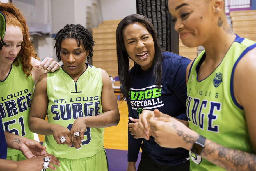 Khalia Collier and St. Louis Surge players laugh while prepping for a photoshoot.