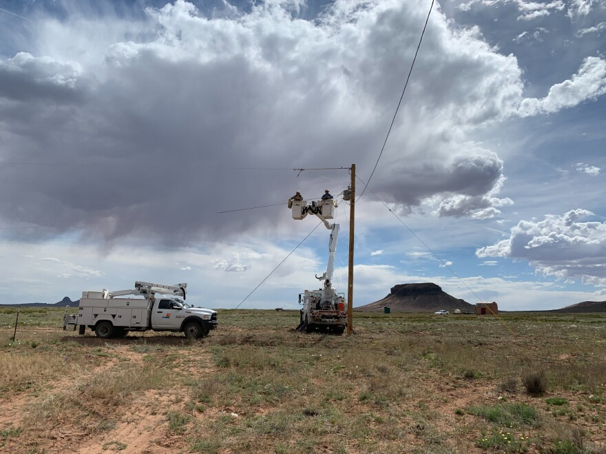 A crew from PNM Electric hooks up a power line to the Billies' home. On the Navajo Nation, the homes are so spread out that it costs $40,000 on average to hook up one home to the electrical grid.
