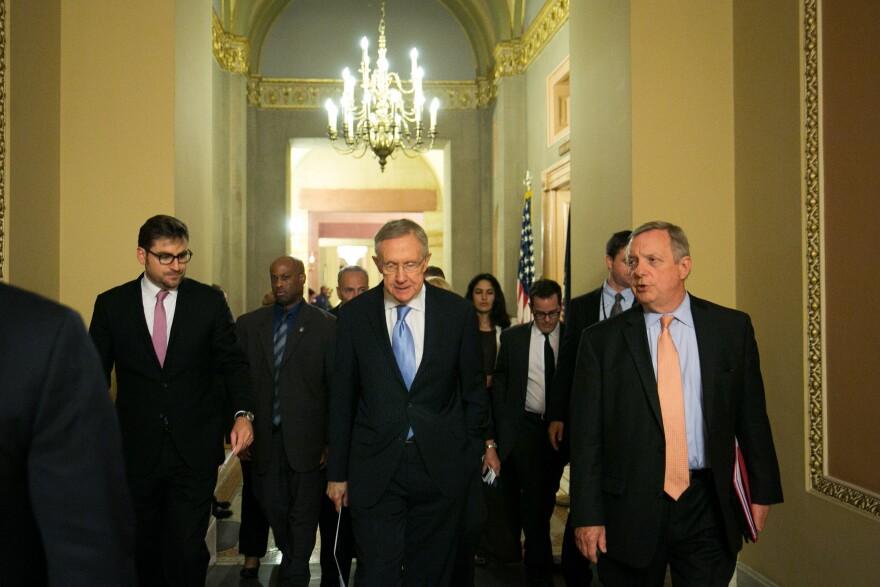 Senate Majority Leader Harry Reid walks with Sen. Dick Durbin of Illinois (right) after a joint caucus meeting on Monday.