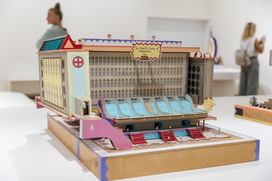 <em>The Scientific Center of Hospitalisation the SIDA.</em> In this 1991 work, Kingelez presents his vision of an integrated hospital and lab facility that would respond to the AIDS crisis (<em></em>SIDA is the French acronym) while also projecting a sense of beauty.