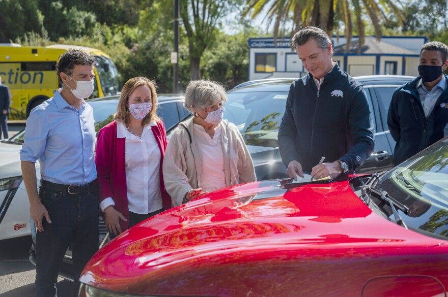 On the hood of an electric car in Sacramento on Wednesday, California Gov. Gavin Newsom signed an executive order requiring all new passenger vehicles sold in the state to be zero-emission by 2035.