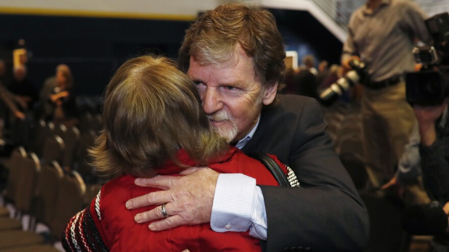 Jack Phillips, owner of Masterpiece Cake, is hugged by a supporter after a rally on the campus of a Christian college in November.