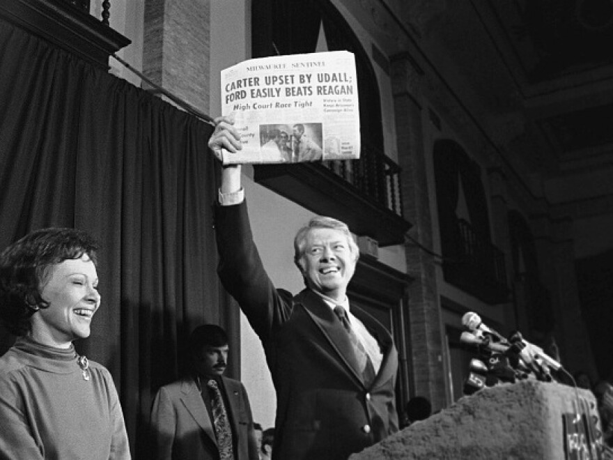 Jimmy Carter holds up an early edition of the <em>Milwaukee Sentinel,</em> which declared Rep. Morris Udall winner of the 1976 Democratic primary. Late returns gave the state to Carter.