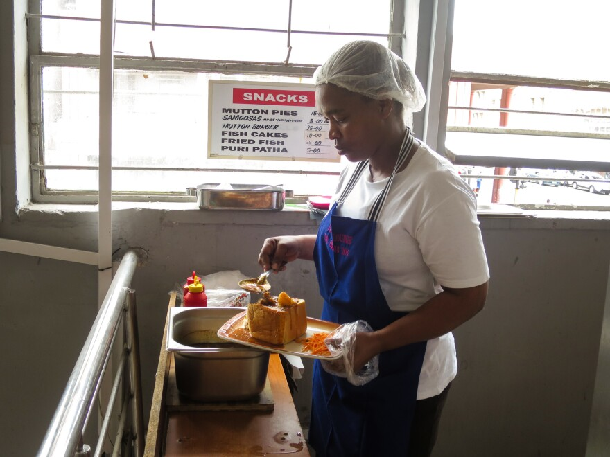 Server Olgah Hlophe scoops some mutton curry into a hollowed-out loaf of bread to make a bunny at the Victory Lounge in Durban.